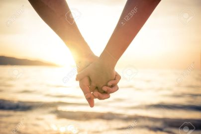 40823041-Couple-of-lovers-holding-their-hands-at-a-beautiful-sunset-over-the-ocean-Newlywed-couple-on-a-roman-Stock-Photo